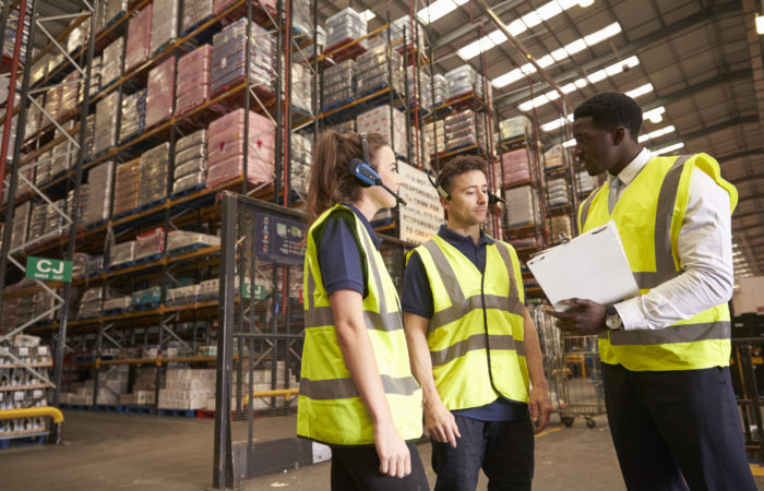 Distribution Warehouse Manager In Discussion With Colleagues